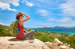 Tourist with backpack sit on a rock on clear sky background, loo Stock Image