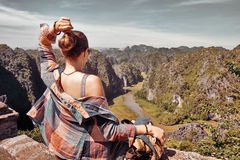 Tourist with backpack sitting on top of the mountain enjoying ri Stock Photography