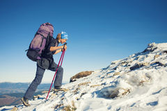 Tourist with a backpack is the snowy slope. Royalty Free Stock Image