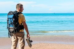 Tourist with a backpack spends vacation on the beach. Admires a beautiful view Stock Images