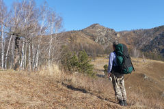 The tourist with a backpack standing at the foot of the mountain Stock Photo