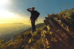 Tourist with  backpack standing on a mountain top enjoys the view of the valley on a sunny day. Tourist with backpack standing on a mountain top enjoys the view Stock Photography