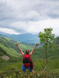 Tourist with backpack standing near the tree with their hands up against a background of mountains Stock Photography