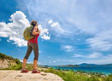 Tourist with backpack standing on a rock on clear sky background Stock Photography