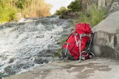 Tourist backpack stands near a mountain river stock images