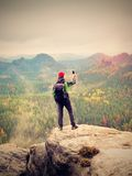 Tourist with backpack stayon cliff and  takes photos with smart phone of rainy valley. Royalty Free Stock Images