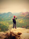 Tourist with backpack stayon cliff and  takes photos with smart phone of rainy valley. Royalty Free Stock Image