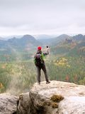 Tourist with backpack stayon cliff and  takes photos with smart phone of rainy valley. Royalty Free Stock Photo