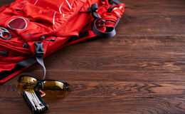Tourist backpack, sunglasses and gear for the bicycle on the wooden background. Set for travel: orange tourist backpack, sunglasses and gear for the bicycle on royalty free stock photos