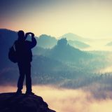 Tourist with backpack takes photos with smart phone on peak of rock. Dreamy fogy valley below Stock Photography