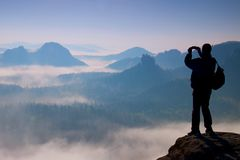 Tourist with backpack takes photos with smart phone on peak of rock. Dreamy fogy valley below Stock Images