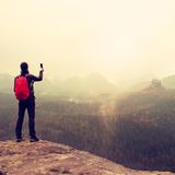 Tourist with backpack takes photos with smart phone of rainy vally. Dreamy foggy valley below Royalty Free Stock Image