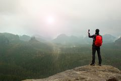 Tourist with backpack takes photos with smart phone of rainy vally. Dreamy foggy valley below Royalty Free Stock Images