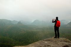 Tourist with backpack takes photos with smart phone of rainy vally. Dreamy foggy valley below Royalty Free Stock Photo