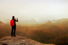 Tourist with backpack takes photos with smart phone of rainy vally. Dreamy foggy valley below Stock Images