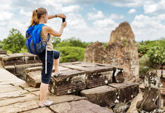 Tourist with backpack taking picture in Angkor, Cambodia Royalty Free Stock Photos