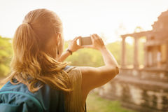 Tourist with backpack taking picture of Angkor Wat, Cambodia Royalty Free Stock Images