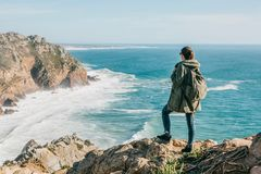 A tourist with a backpack on top of a cliff admires a beautiful view of the Atlantic Ocean in Portugal stock photos