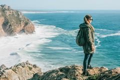 A tourist with a backpack on top of a cliff admires a beautiful view of the Atlantic Ocean in Portugal royalty free stock photography