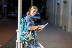 Tourist with backpack in the town holding a map. Young male tourist with backpack standing in the town with a guide Royalty Free Stock Images
