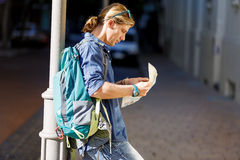 Tourist with backpack in the town holding a map. Young male tourist with backpack standing in the town with a guide Royalty Free Stock Photos