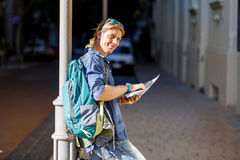 Tourist with backpack in the town holding a map. Young male tourist with backpack standing in the town with a guide Royalty Free Stock Image