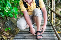 tourist with a backpack zips up sandals Royalty Free Stock Image