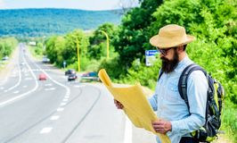 Tourist backpacker looks at map choosing travel destination at road. Around the world. Find map large sheet of paper. Allow recognize enough details to walk stock photography