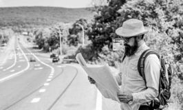 Tourist backpacker looks at map choosing travel destination at road. Around the world. Find map large sheet of paper. Allow recognize enough details to walk stock photo