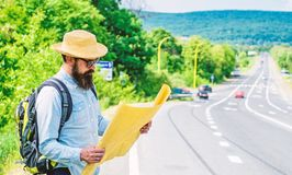 Tourist backpacker looks at map choosing travel destination at road. Around the world. Find map large sheet of paper. Allow recognize enough details to walk royalty free stock images