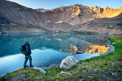 Tourist Backpacker in the mountains. Bearded man in green hat and backpack looking at mountain lake at sunrise Royalty Free Stock Images