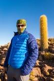 Tourist backpacker standing mountain huge cactus, Salar De Uyuni, Bolivia. Man tourist backpacker wearing balaclava mask hat covered face standing mountain next royalty free stock image