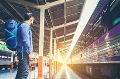 Tourist backpacker wait to travel at train station.  royalty free stock image