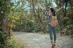 Tourist backpacker walking in national park. Attractive young tourist backpacker walking in national park and opening hands enjoying nature atmosphere at summer Royalty Free Stock Image