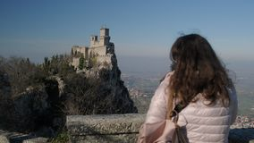 Tourist with bag looks at Fortress of Guaita tower. Woman tourist with cross body bag looks at Fortress of Guaita tower surrounded by trees over city stock footage