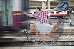Tourist with bag running behind the train. A man runs for a moving wagon. Backpacker hurries for train departing from the station. Journey to the last minute stock images