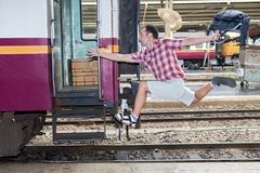 Tourist with bag running behind the train. A man runs for a wagon. Backpacker hurries for train departing from the station. Journey to the last minute stock photo