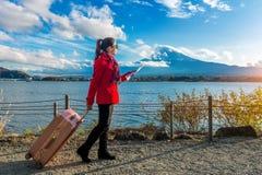 Tourist with baggage and map at Fuji mountain, Kawaguchiko in Japan.  royalty free stock image