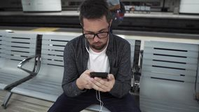Tourist in Barcelona Underground waiting for transport. Close-up portrait of a man in glasses sitting on bench and listening to music on his smartphone in stock video footage