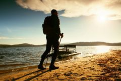 Tourist on beach at old paddle boat. Man with poles  in warm sporty clothing at sunset. Autumn weather. Royalty Free Stock Photo