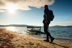 Tourist on beach at old paddle boat. Man with poles  in warm sporty clothing at sunset. Autumn weather. Stock Photo