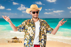 Tourist on the beach. A young, attractive male in a colorful outfit in a tropical island setting as a stereotype tourist stock image