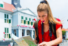 Tourist being lost in Jakarta, Indonesia. Woman got lost sightseeing with touristic map in Jakarta, Indonesia Stock Images
