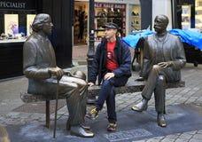 Tourist on the bench with Irish writer Oscar Wilde Royalty Free Stock Photo