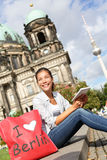 Tourist in Berlin, Germany on travel. Reading guidebook. Woman sitting with shopping back saying I LOVE BERLIN smiling happy in front Berlin Cathedral / Stock Photo