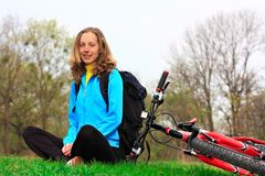 Tourist with a bicycle and a backpack to a halt Royalty Free Stock Image