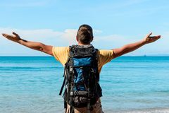 Tourist with a big backpack on the beach with outstretched hands. To the es enjoy a beautiful view Stock Photo