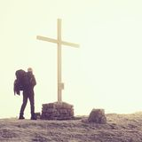 Tourist with big backpack stand at cross memorial on mountain peak. Man is watching into misty Alpine valley bellow. Metal cross. Stock Image