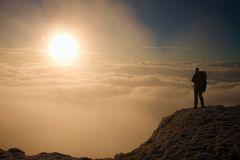 Tourist with big backpack is standing on view point and watching into misty valley. Sunny winter morning. Stock Image