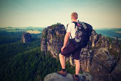 Tourist with big backpack. Sunny evening in rocks of Saxony Switzerland park. Hiker stand on rocky view point above valley. Royalty Free Stock Image